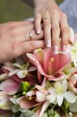 Wedding rings and hands at the wedding bouquet — Stock Photo