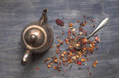 Antique teapot and strawberry tea on dark wooden background — Stock Photo
