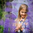 Beautiful laughing girl in a field of purple lupine flowers. — Stock Photo #75287247