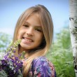 Beautiful laughing girl in a field of purple lupine flowers. — Stock Photo #75287801