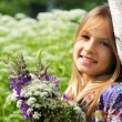 Beautiful laughing girl in a field of purple lupine flowers. — Stock Photo #76074339