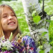 Portrait of a beautiful dreaming girl with a bouquet of flowers. Some white birch — Stock Photo #76075465