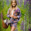 Beautiful laughing girl in a field of purple lupine flowers. — Stock Photo #76077137