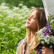 Portrait of a beautiful dreaming girl with a bouquet of flowers. Some white birch — Stock Photo #76077397
