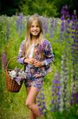 Beautiful laughing girl in a field of purple lupine flowers.  — Stock Photo