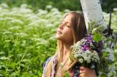 Portrait of a beautiful dreaming girl with a bouquet of flowers. Some white birch — Stock Photo