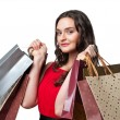 Smiling woman in red dress with shopping bags — Stock Photo #71653203