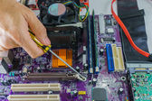 Technician's hands fixing mainboard with screwdriver — Stock Photo