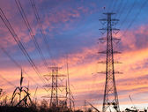 Parallel high voltage electricity pylon on the orange sky in the evening. — Foto de Stock