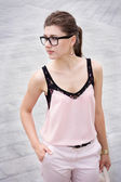 Girl in stylish clothes wearing glasses outside. — Stock Photo