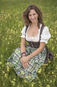Woman with dirndl in flower meadow — Foto Stock
