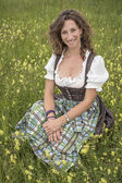 Woman with dirndl in flower meadow — Photo