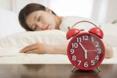 Woman sleeping in bed beside alarm clock — Stock Photo