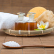 Spa bath, salt spoon, towel sponge essential oil and flower for — Stock Photo #79153882