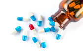 Blue capsules and red capsules with  bottle, healthcare and medi — Stock Photo