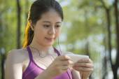 Sporty asian woman listening music after jogging in the  forest — Stock Photo