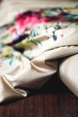 Beautiful satin textile with flowers on wooden background — Stock Photo