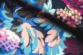 Färgglad textil rulla med blommor på trä bakgrund — Stockfoto