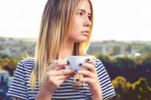 Beautiful young woman in casual wear dreaming with cup of hot coffee — Stock Photo