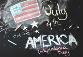 Black chalkboard in classroom with American flag...4 th of July — Stock Photo