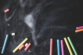 Black old empty chalkboard for copy space with colorful pieces of chalk — Stock Photo