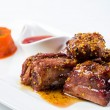 Barbecued pork ribs served with tomato sauce and carrot puree  isolated on white background — Stock Photo #77936214