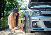 Young woman checks wheel of the car — Stock Photo