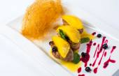 Pan seared foie gras on ripe mango and pomegranate reduction. white plate — Stock Photo