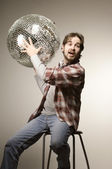 Young man posing with a disco ball — Stock Photo