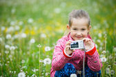 Little smiling girl proudly showing her photograph — Stock Photo