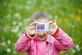 Little girl making a selfie with digital camera — Stock Photo