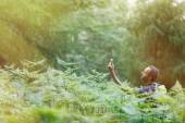 Geocaching in sunlit forest — Stock Photo