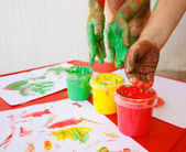 Children dipping fingers in washable finger paints — Stock Photo