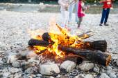 Family enjoying time by the river and self-made campfire — Stock Photo