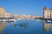 Fishing boats and kayakers in the darsena of Ortigia Islet from the Bridge Umbertino. On the background the skyline of Siracusa on the mainland — Stock Photo