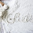 Word gluten on wood board with flour — Stock Photo #76196083