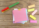 Colored stickers around notebook on old wooden table — Stock Photo