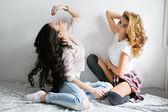 Две молодые красивые девушки смеются и позирует в спальне сидят — Стоковое фото
