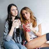 Two young beautiful girls laughing and posing with cups and inha — Stock Photo