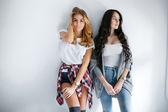 Две молодые красивые девушки смеются и позирует на фоне стены — Стоковое фото