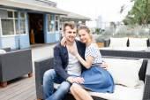 Una joven pareja pasa tiempo en el sofá en la cafetería al aire libre — Foto de Stock