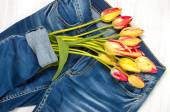 Bouquet of colored tulips and blue jeans on the light background — Stock Photo
