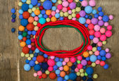 Red circle and multicolored beads made of wool merino on the wooden background. Place for text — Stock Photo