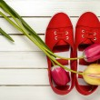Red shoes and a bouquet of tulips on a white wooden background — Stock Photo #79869904