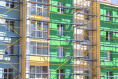 Scaffolding for finishing work the walls of a multistory building — Stock Photo