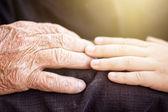 Nephew touching grandfather's hand in sunlight — Stock Photo