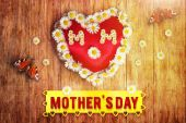 Greeting card of heart with marguerites and butterflies on wooden board — Stock Photo