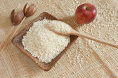 White rice as natural ingredient on a wooden cup, country scene — Stock Photo