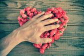 Cuore fatto delle rose rosse in fondo di legno, coperto da una mano — Foto Stock