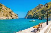 Bench, isthmus sea in port of Vathi Greek Island — Stock Photo